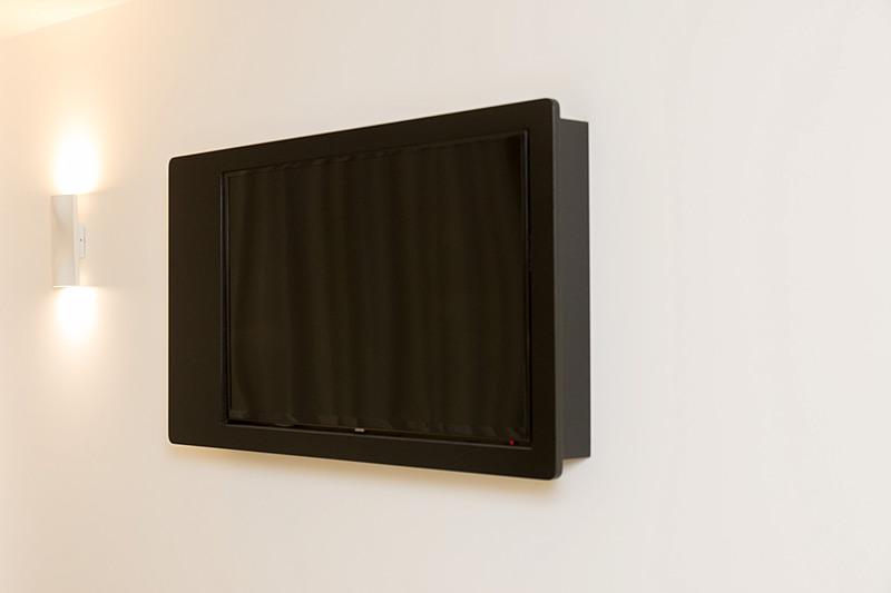 42インチテレビはワークデスクの上部の壁に設置されている