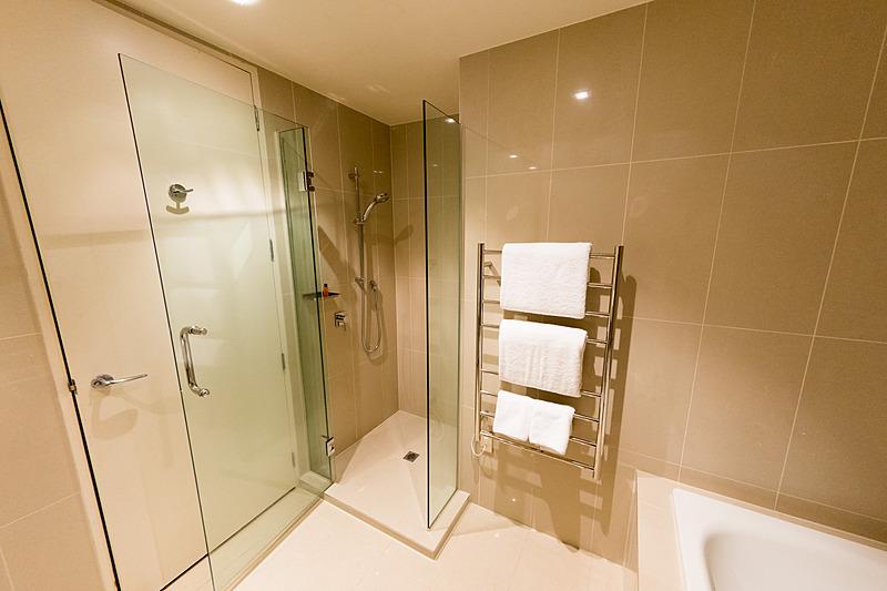 バスタブとシャワーブースを備える広いバスルーム。タオルウォーマーが便利