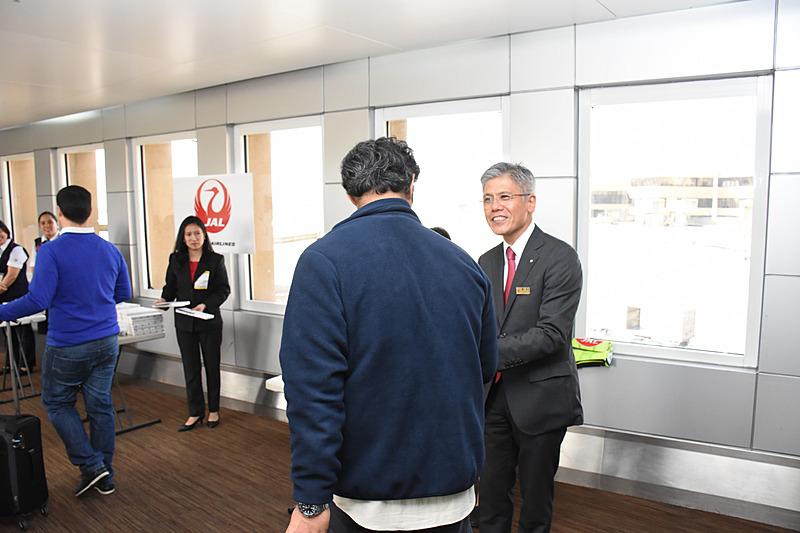 搭乗客に記念品をプレゼントする藤田副社長と現地スタッフ