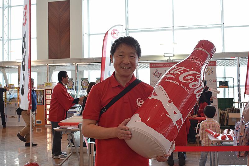 日本航空株式会社 東京2020オリンピック・パラリンピック推進部長 小西一史氏。限定デザイン缶のビッグダミーを抱えてアピール