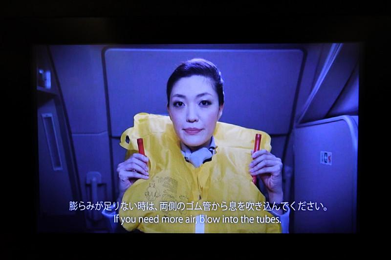 座席下にある救命胴衣を着用し、ふくらみが足りないときは左右のゴム管から息を吹き込んでふくらませる