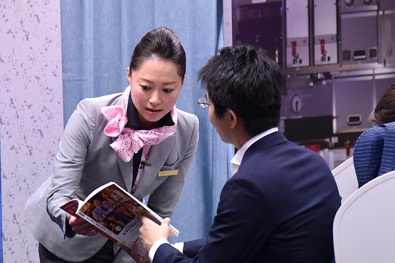 雑誌を見てほしいとの乗客のリクエストに答えつつ機内の日本酒の話にスムーズにつなげていた