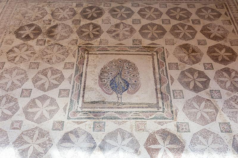 幾何学模様の中心にクジャクが立つ。天然石ながらクジャクの色彩が見事