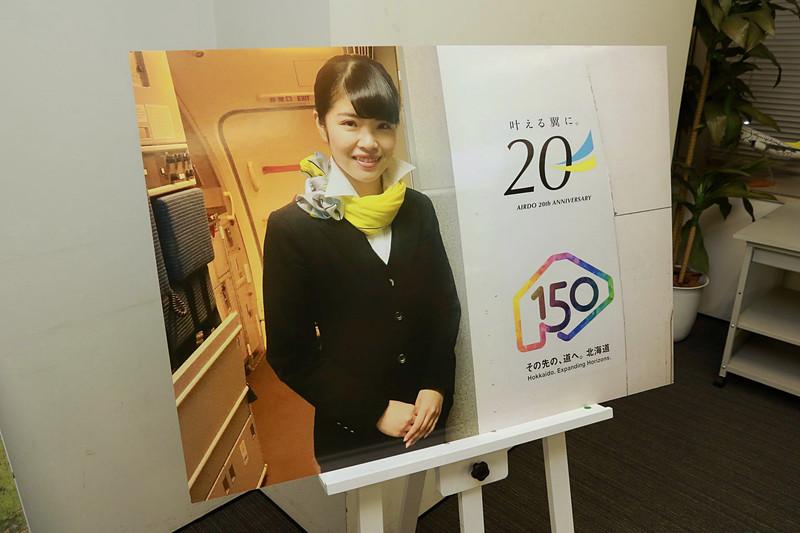 CA(客室乗務員)の立つ機体搭乗口の横に貼ってある就航20周年ロゴマーク(上)と北海道命名150年ロゴマーク(下)の掲出は、2018年12月まで実施予定だ