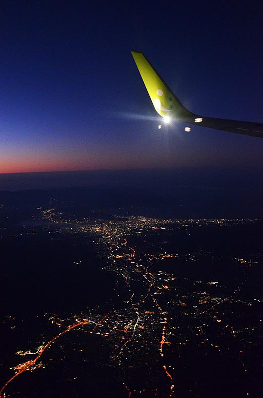 眼下は都会の夜景。でも東の空は明るくなっています