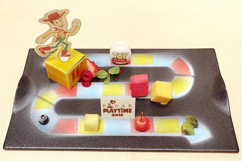 ボードゲームが描かれたプレートにデザートが広がる「チョコレートケーキ ラズベリーとマンゴーのソルベ」