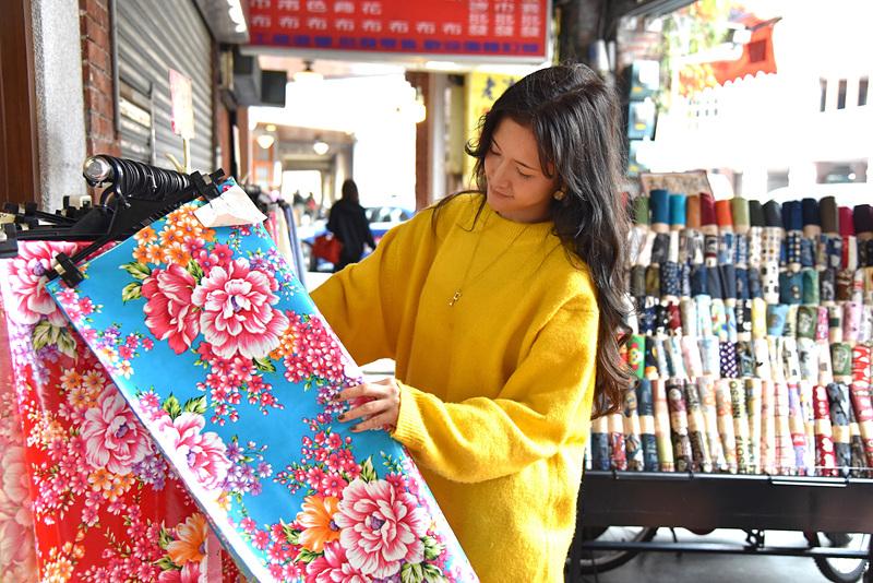 鮮やかな色合いの客家布を手にするFukiさん。気になる柄は見付かりましたか?