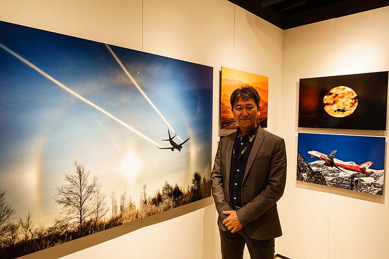 中野耕志氏、主に旅客機の作品が飾られているエリアで。向かって左が新千歳空港付近で撮影した作品