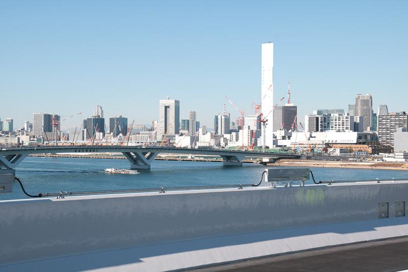 並行する環状2号線の豊洲大橋。橋を渡った先に見えるクレーンの数々は、2020年オリンピック・パラリンピックの選手村の建設機材