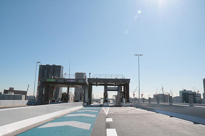 10号晴海線の豊洲入口と晴海入口は並んでいる。現在の路面のマーキングは豊洲入口側が主線となっているが、追々は晴海入口側を主線に変更するとのこと。東京湾に向かって右手に見えるクレーン群は、2020年東京オリンピック・パラリンピックの競技場の建設機材