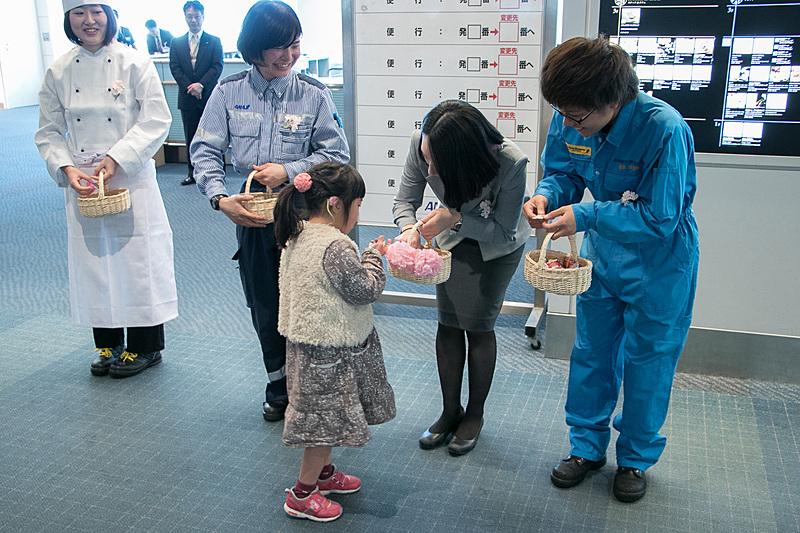 ANAグループ各部門の女性スタッフが、乗客にお菓子を配る