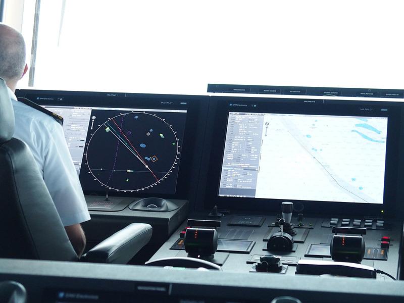 当直士官コンソールと電子海図とAIS情報を重畳表示した電子航法支援システムディスプレイ。手前に見えるのはスラスター操作用ジョイスティックと機関出力を制御するスロットル