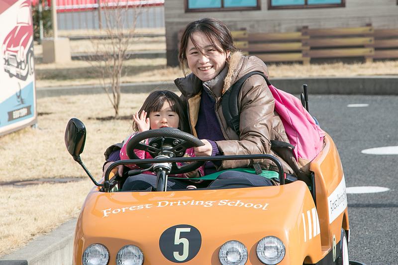 市街地コースをドライブしながら交通ルールを学ぶ「森の教習所」。「止まれ」の標識では一時停止して安全を確認