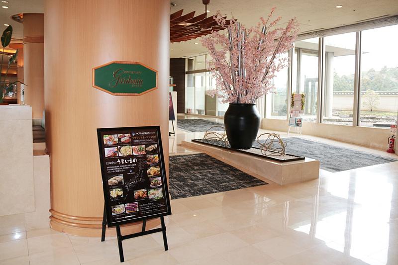 バラエティあふれるビュッフェ料理を提供する1階の「ガーデニア」と24時間営業の「ファミリーマート」。ロビーの公衆電話の上には世界各国の時刻を表示する時計があった