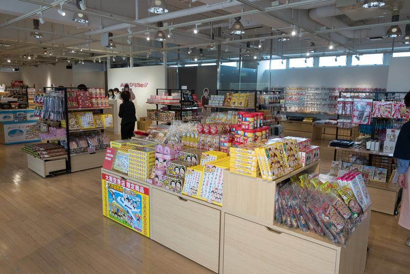 伊丹空港限定品が充実している「よしもとエンタメショップ」。「吉本新喜劇/プリントクッキー」や「ショッピングバッグ」のほか、NMB48とのコラボTシャツを販売