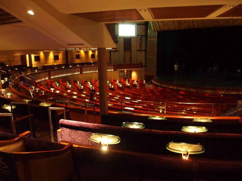 客席数1100人のデッキ三層にまたがる船内劇場。シートにはテーブルを用意して飲み物を楽しみながら観劇できる