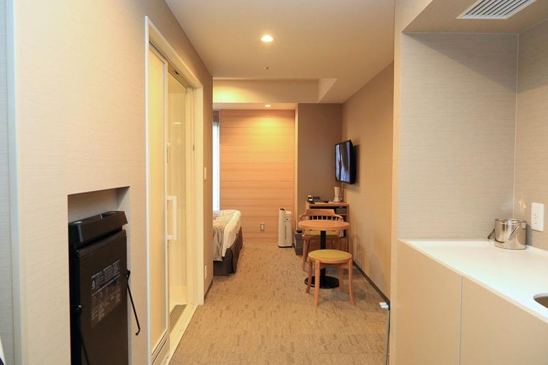 車いすでの移動ができるよう部屋の通路の幅を確保したミニキッチン付きの客室。トイレには呼び出しボタンが配置されておりフロントと連動している。