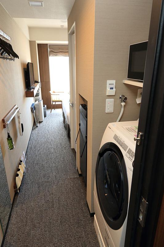 部屋に入ると洗濯機や電子レンジが顔を出す。洗濯機の横にはズボンプレッサーが壁に備え付けてある