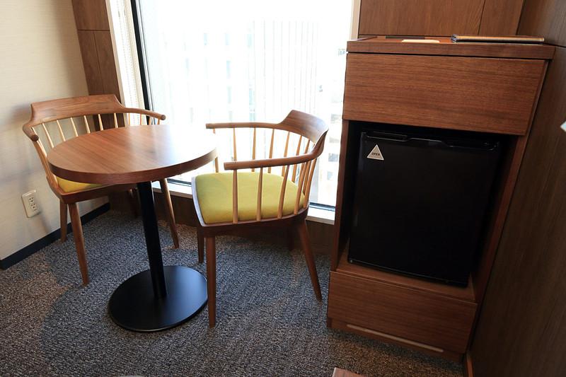 窓際には椅子が2脚とテーブル、右には冷蔵庫