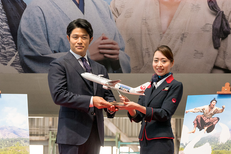 JALのCAから鈴木亮平さんへ西郷どん特別塗装機のモデルプレーンを贈呈