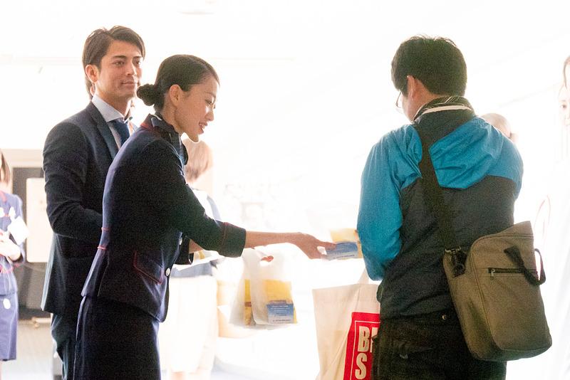 搭乗ゲートで鈴木亮平さんもお見送り。一人一人と握手をかわし、ポストカードをプレゼント。JALのスタッフからもお菓子が配布された