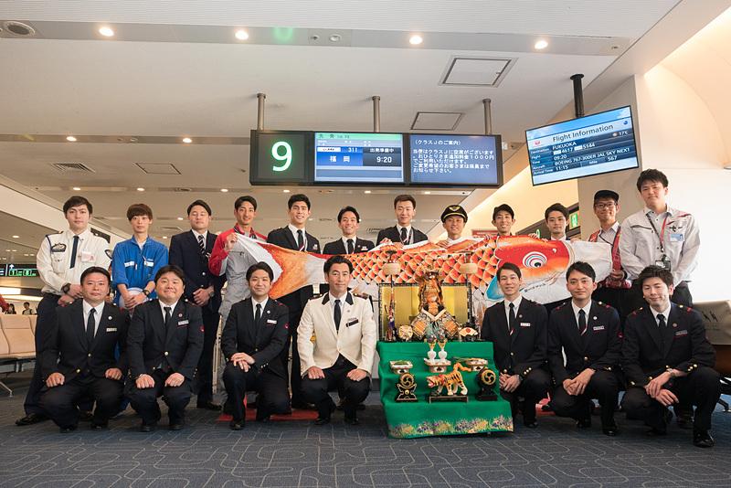 搭乗口まわりでのイベントに参加したさまざまな職種のスタッフ(後列)と、こいのぼりフライトの乗務員(前列)による記念撮影
