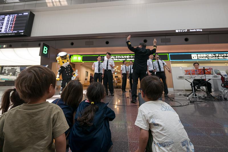 JALスマイルサポート前でのパフォーマンスでは子供を中心に多くの人が見学。パイロットから子供たちにシールが送られた。普段は乗客と接する機会が少ないパイロットにとっても貴重な機会になっている