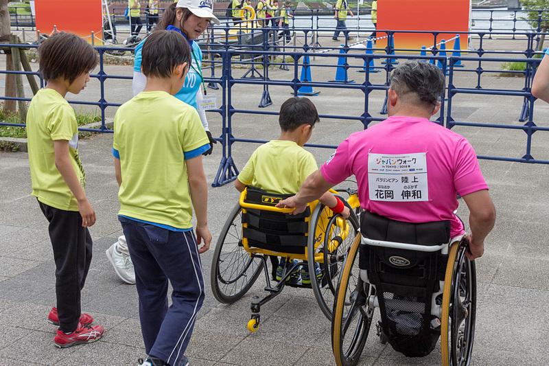 集まってきた子供たちにレース用車いすの操作方法を教える花岡伸和さん