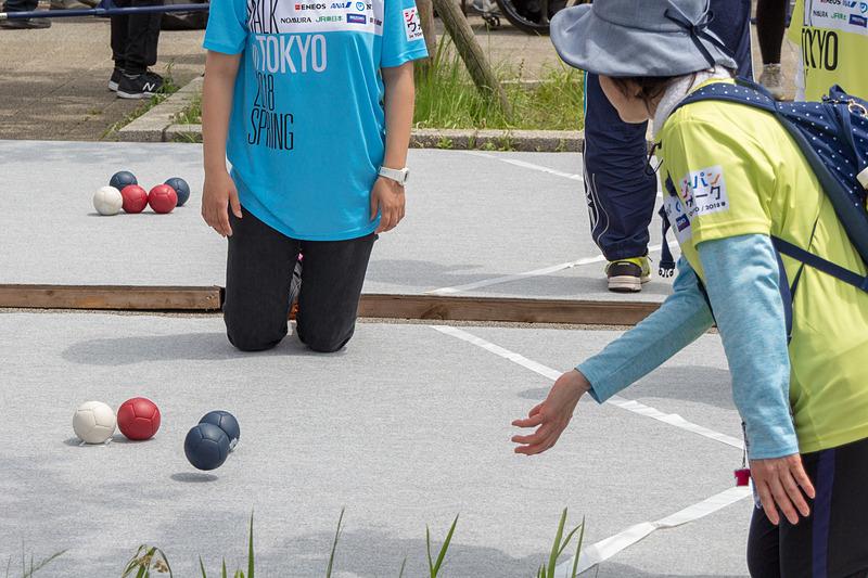 ボッチャはカーリングのように、いかに多くの球を目標球に近づけるかを競う。投げることができない人は蹴ったり、用具を使ったりすることも認められている