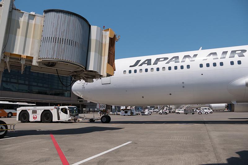 PBB(旅客搭乗橋)が外れプッシュバックを開始。JALグループスタッフが地上から手を振ってお見送り