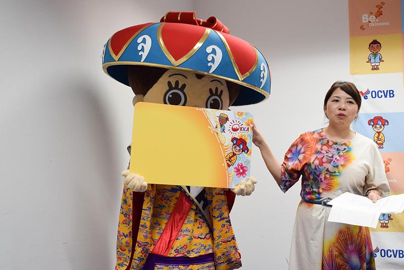 新デザインOKICAの拡大版をお披露目する花笠マハエちゃん