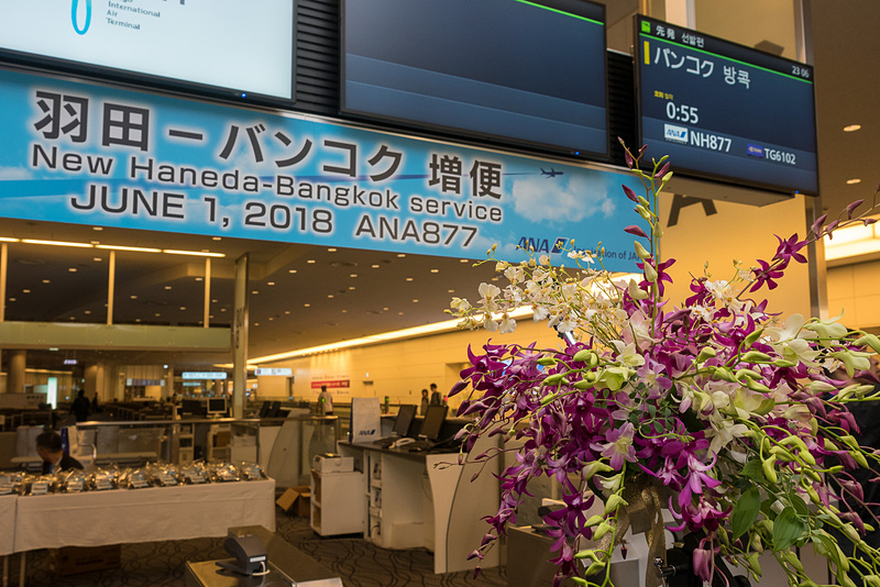 セレモニーは羽田空港国際線ターミナル108番搭乗口で実施。マイクやパネルの装飾のほか、CA(客室乗務員)や地上旅客スタッフのコサージュとしてデンファレの花が彩りを添えた