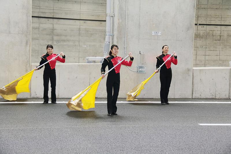 市川昴高校吹奏楽部の演奏をバックに特設ゲートを通過する各車両。窓を開け手を振る関係者も多かった