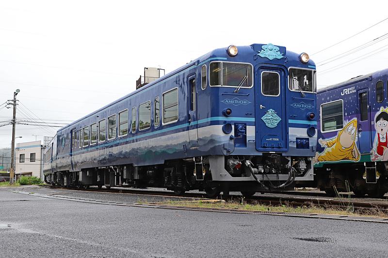 撮影時は曇天のため深い青に見えたが、晴天だと異なった趣になりそうだ。隣に停車しているのは境港線 鬼太郎列車「子泣き爺車両」