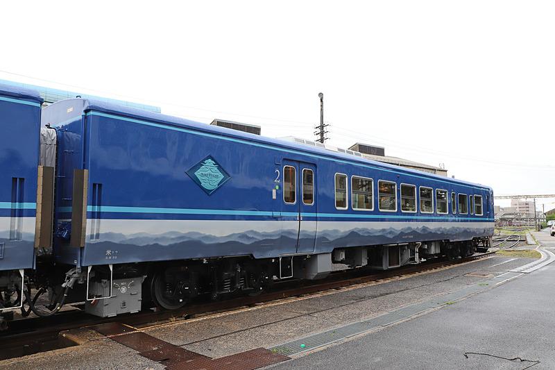 1号車(写真左)と2号車(写真右)の側面。帯模様は山並みにも日本刀の刃文にも見える