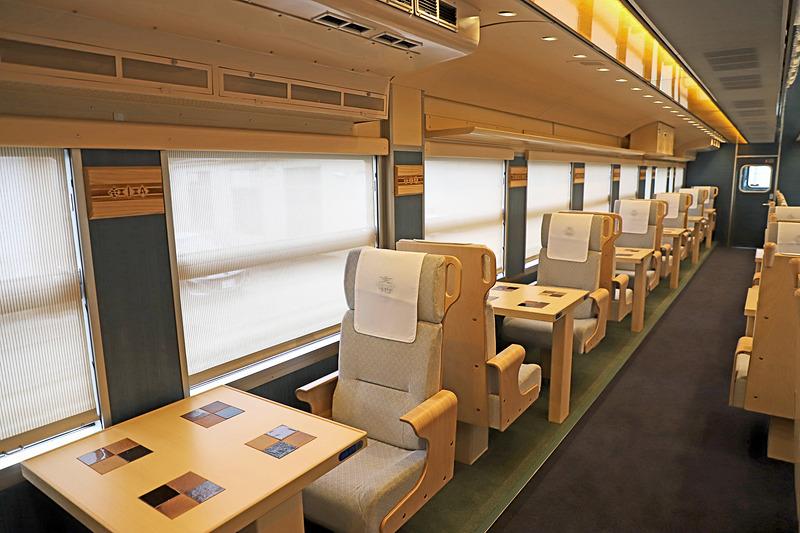 1号車(写真左)と比較して2号車(写真右)の対面シートの一部は、さらに一段高くなっている。鳥取県をイメージした2号車のみの通称「大山シート」だ