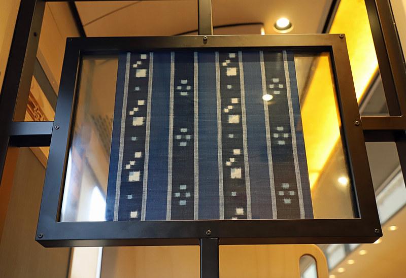 1号車ドア付近に展示された織物。写真左は出雲織、写真右は安来織で、いずれも島根県安来市で制作されたもの