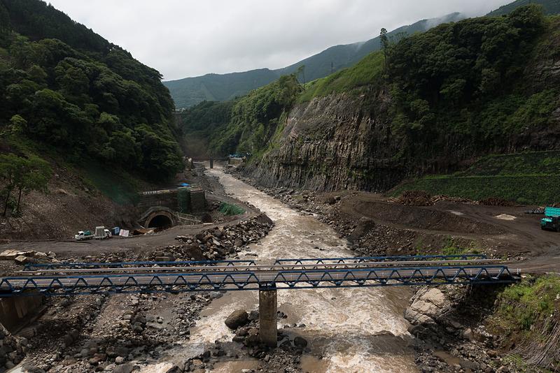 立野ダム建設予定地の上流側にある橋からの眺め。前方奥にある低い仮設橋がダムの建設予定地、右側の崖の特異な形状が柱状節理と呼ばれるもの。左下に見えるトンネルは仮排水路トンネルと呼ばれるもので詳しくは後述する
