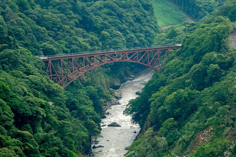 北向き山原生林に浮かび上がる赤いアーチ橋、南阿蘇鉄道 第一白川橋梁