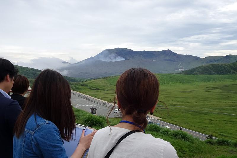 奥に中腹から噴煙を上げる中岳を望める