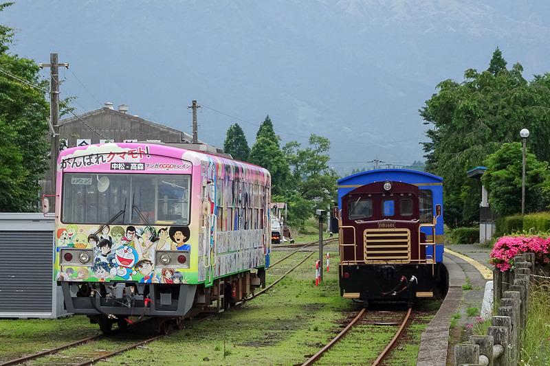 南阿蘇鉄道のトロッコ列車の旅へ。写真は高森駅に停車する「がんばれクマモト! マンガよせがきトレイン」(左)と、トロッコ列車「ゆうすげ号」(右)