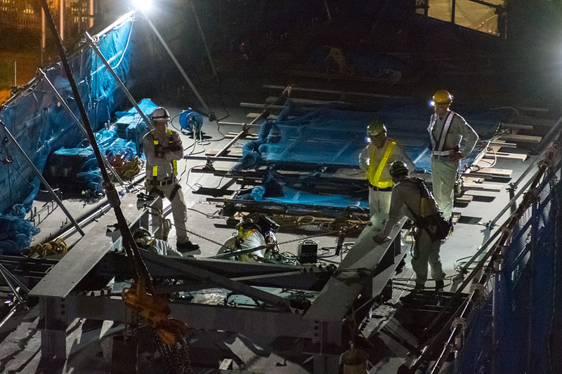 桁を吊り上げたままの状態で、ボルトの締め付けや足場の設置作業が進められる