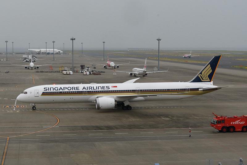 到着し、搭乗ゲートへ向かうシンガポール航空 ボーイング 787-10型機。奥には、787シリーズの構造部品を運ぶ、ボーイング 747LCF ドリームリフターが見える