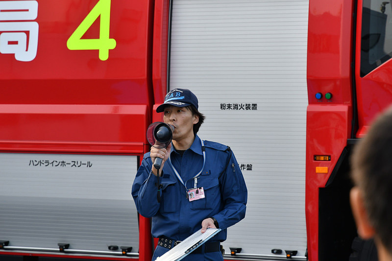 消防職員から見学内容について説明。今回は消防車の運転台体験と放水デモが用意されていた