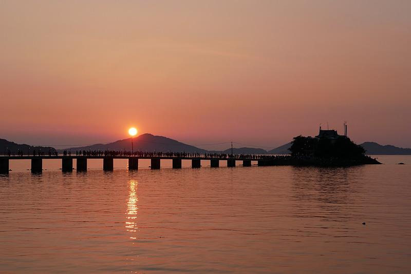 夕暮れ時、津嶋神社の奥に沈む夕日に赤く染められた空や海と、津嶋神社のシルエットも必見の美しさだ