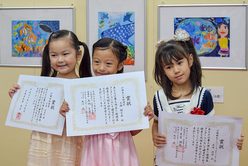 日本トランスオーシャン航空が「第3回美ら海図画コンクール」表彰式を行なった。受賞者したのは、左から三木はるかさん、永瀬瑠々花さん、石﨑結唯さん