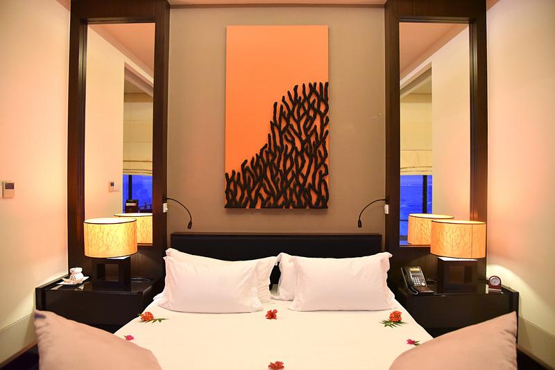 部屋の中央にキングサイズのベッドが鎮座。ターンダウン前は花々でデコレーション
