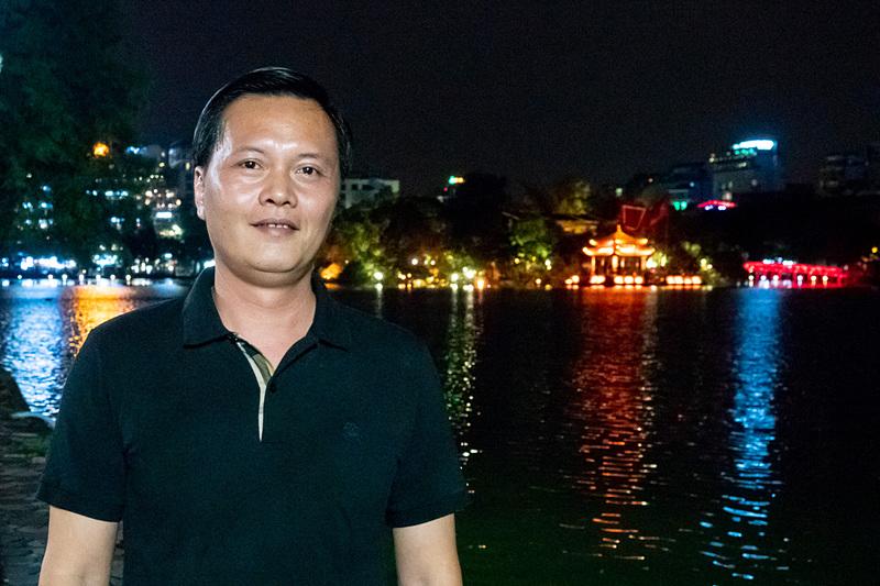 ハノイ観光局 局長のチャン・ドゥック・ハイ氏。背にするのはハノイ旧市街の中心部にある主要観光スポット「ホアンキエム湖」の夜景