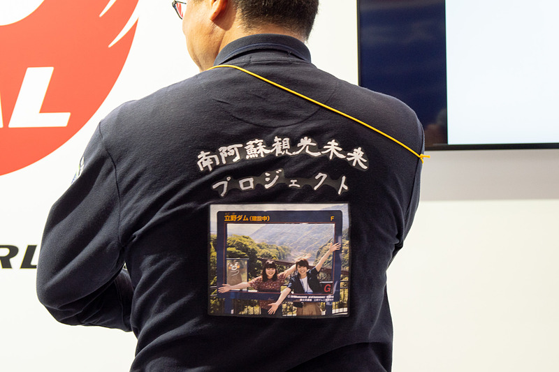 防災服の下から「立野ダムマイフォトカードフレーム」をプリントしたシャツが登場