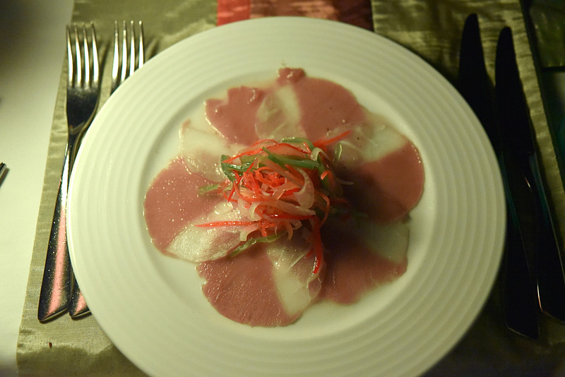 「Thinly Sliced Carpaccio of Smoked Marlin, Sauteed Marinated Baby Octopus, Tiger Prawns Sea Bass and Mussel served with Cocktail Sauce, Kopi Fai and Salad Leaf」
